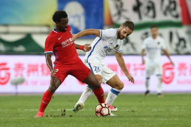 Brazilian football player Fernandinho, left, of Chongqing Dangdai Lifan kicks the ball to make a pass against Spanish football player Mario Suarez of Guizhou Hengfeng Zhicheng in their 20th round match during the 2017 Chinese Football Association Sup