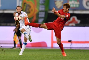 Spanish football player Mario Suarez, left, of Guizhou Hengfeng Zhicheng kicks the ball to make a pass against a player of Chongqing Dangdai Lifan in their 20th round match during the 2017 Chinese Football Association Super League (CSL) in Guiyang ci