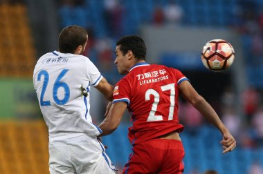 Spanish football player Mario Suarez, left, of Guizhou Hengfeng Zhicheng heads the ball to make a pass against Croatian football player Alan Kardec of Chongqing Dangdai Lifan in their 20th round match during the 2017 Chinese Football Association Supe