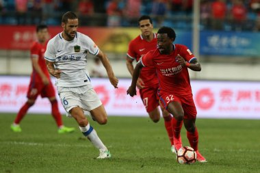 Brazilian football player Fernandinho, right, of Chongqing Dangdai Lifan kicks the ball to make a pass against Spanish football player Mario Suarez of Guizhou Hengfeng Zhicheng in their 20th round match during the 2017 Chinese Football Association Su