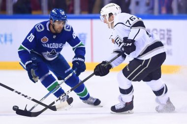 Jonny Brodzinski, right, of Los Angeles Kings competes against Brandon Sutter of Vancouver Canucks during the second NHL China preseason hockey game at Wukesong Arena in Beijing, China, 23 September 2017