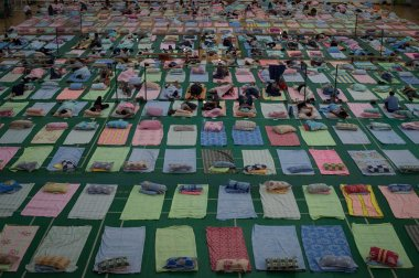 Aerial view of parents of freshmen students who escorted their children for enrollment on their first day of study resting on mats laid out on the floor at a gymnasium of South-central University For Nationalities in Wuhan city, central China's Hubei