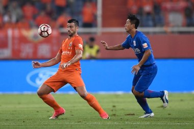 Italian football player Graziano Pelle, left, of Shandong Luneng kicks the ball to make a pass against a player of Shanghai Greenland Shenhua in their 22nd round match during the 2017 Chinese Football Association Super League (CSL) in Ji'nan city, ea