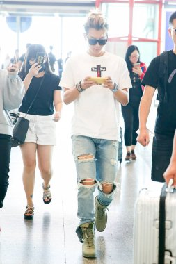 Chinese singer and actor Huang Zitao, better known as Z.TAO, plays a mobile game on his smartphone at the Beijing Capital International Airport in Beijing, China, 24 August 2017.