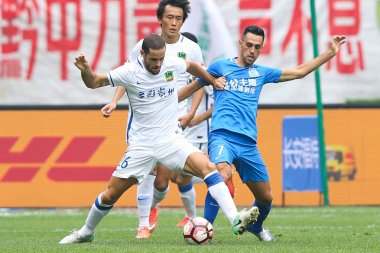 Israeli professional football player Eran Zahavi, right, of Guangzhou R&F, challenges Spanish football player Mario Suarez of Guizhou Hengfeng Zhicheng in their 22nd round match during the 2017 Chinese Football Association Super League (CSL) in Guiya