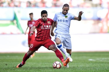 Brazilian football player Givanildo Vieira de Sousa, better known as Hulk, left, of Shanghai SIPG, challenges Spanish football player Mario Suarez of Guizhou Hengfeng Zhicheng in their 23rd round match during the 2017 Chinese Football Association Sup