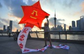 Chinese kite lover Mr. Gu flies the kite featuring the figure of five-pointed star and characters of Bayi to celebrate the 90th founding anniversary of the Peoples Liberation Army (PLA) at the Siqhtseeing Platform of the Bund in Shanghai, China,