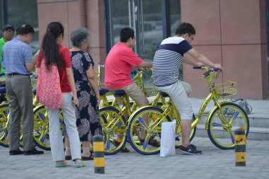 Local residents use their smartphones to scan QR codes on golden bicycles of Chinese bike-sharing service Coolqi is displayed on a road in Shenyang city, northeast China's Liaoning province, 8 August 2017