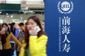 Passengers walk past an advertisement of Foresea Life Insurance (QHL) at a metro station in Shanghai, China, 7 December 2014