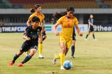 Riko Ueki of Japan, left, challenges Chen Qiaozhu of China in their semi-final 2 match during the AFC U-19 Women's Championship China 2017 in Nanjing city, east China's Jiangsu province, 25 October 2017