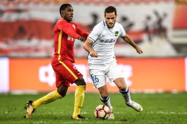 Nigerian football player Odion Ighalo, left, of Changchun Yatai challenges Spanish football player Mario Suarez of Guizhou Hengfeng Zhicheng in the 27th round match during the 2017 Chinese Football Association Super League (CSL) in Guiyang, southwest