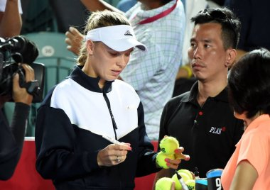 Danish tennis player Caroline Wozniacki, left, signs her autographs on tennis balls for spectators after she announced her withdrawal from Prodential Hong Kong Tennis Open 2017 due to injury during a training session in Hong Kong, China, 12 October 2