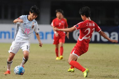 Riko Ueki, left, of Japan kicks the ball to make a pass against Ju Hyo Sim of DPR of Korea in their final match during the AFC U-19 Women's Championship China 2017 in Nanjing city, east China's Jiangsu province, 28 October 2017
