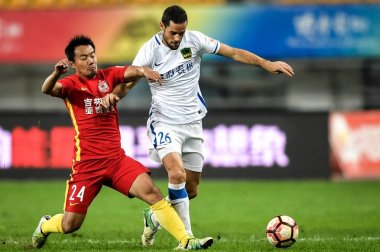 Yan Feng, left, of Changchun Yatai challenges Spanish football player Mario Suarez of Guizhou Hengfeng Zhicheng in the 27th round match during the 2017 Chinese Football Association Super League (CSL) in Guiyang, southwest China's Guizhou province, 14