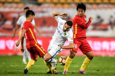 Spanish football player Mario Suarez, center, of Guizhou Hengfeng Zhicheng, challenges players of Changchun Yatai in the 27th round match during the 2017 Chinese Football Association Super League (CSL) in Guiyang, southwest China's Guizhou province,