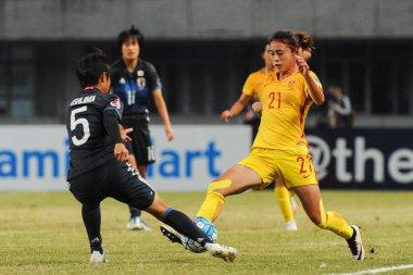 Riko Ushijima of Japan, left, challenges Zhi Jie of China in their semi-final 2 match during the AFC U-19 Women's Championship China 2017 in Nanjing city, east China's Jiangsu province, 25 October 2017