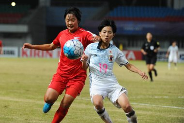 Riko Ueki, right, of Japan kicks the ball to make a pass against a player of DPR of Korea in their final match during the AFC U-19 Women's Championship China 2017 in Nanjing city, east China's Jiangsu province, 28 October 2017