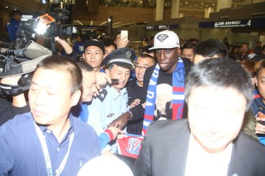 Senegalese striker Demba Ba of Shanghai Shenhua is surrounded by fans after arriving at the Shanghai Pudong International Airport in Shanghai, China, 25 October 2016.