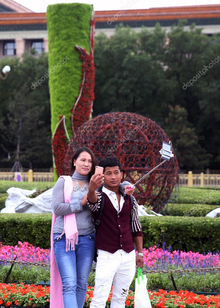 Tourists pose for selfies in front of a giant flower terrace being built on Tian'anmen Square to celebrate the upcoming National Day in Beijing, China, 18 September 2016
