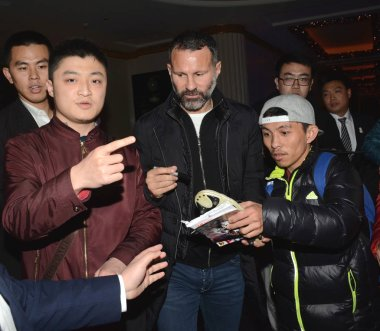 Retired British football star Ryan Giggs, center, is surrounded by fans at a hotel in Shanghai, China, 6 December 2016.