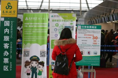 A passenger looks at signboards of Spring Airlines at the Shanghai Pudong International Airport in Shanghai, China, 29 January 2015
