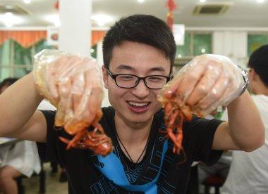 A Chinese graduate eats crayfish at a canteen in Nanjing University of Aeronautics and Astronautics in Nanjing city, east China's Jiangsu province, 30 May 2016