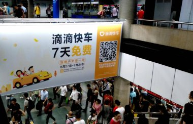 Passengers walk under an advertisement for taxi-hailing and car-service app Didi at a metro station in Shanghai, China, 13 July 2016