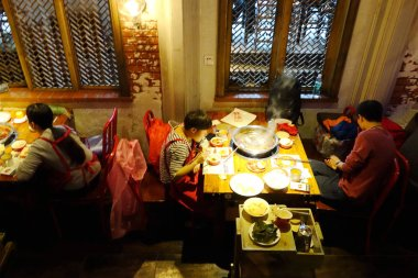 Chinese customers enjoy hot pot at a hotpot restaurant in Chongqing, China, 23 March 2016