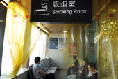 Chinese passengers smoke cigarettes in a smoking room at the Chengdu Railway Station in Chengdu city, southwest Chinas Sichuan province, 31 May 2016