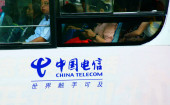 Chinese passengers sit in a bus with an advertisement of China Telecom in Yichang city, central Chinas Hubei province, 7 May 2015