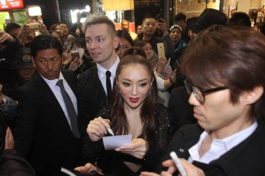 Japanese singer Ayumi Hamasaki, center, signs autographs for fans on a street before midnight in Hong Kong, China, 23 February 2016.