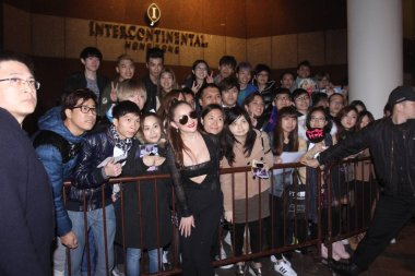 Japanese singer Ayumi Hamasaki, front, poses with fans on a street after midnight in Hong Kong, China, 24 February 2016.