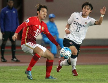 Shim Dong-woon of South Korea's Pohang Steelers FC, right, challenges Rong Hao of China's Guangzhou Evergrande Taobao FC during their Group H 1st round match of the AFC Champions League 2016 in Guangzhou city, south China's Guangdong province, 24 Feb