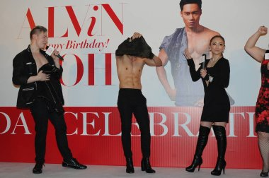 Japanese singer Ayumi Hamasaki, right, reacts next to her stylist friend Alvin Goh, center, taking off his clothes at a celebration event for his birthday in Hong Kong, China, 22 February 2016.