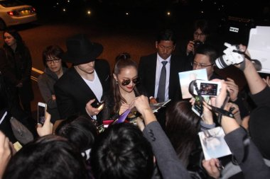 Japanese singer Ayumi Hamasaki, center, signs autographs for fans on a street after midnight in Hong Kong, China, 24 February 2016.