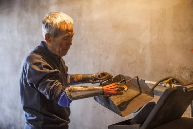 63-year-old armless farmer Sun Jifa who is equipped with his homemade mechanical hands dumps trash into a garbage bin at home in Guanma village, Kouqian town, Yongji county, Jilin city, northeast China's Jilin province, 12 March 2016