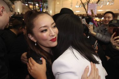 Japanese singer Ayumi Hamasaki, left, hugs a fan on a street before midnight in Hong Kong, China, 23 February 2016.
