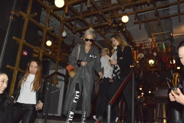 Hong Kong-born American singer Coco Lee, center right, talks with British singer Rita Ora, center left, as she feasts Rita at her restaurant in Hong Kong, China, 22 March 2016.
