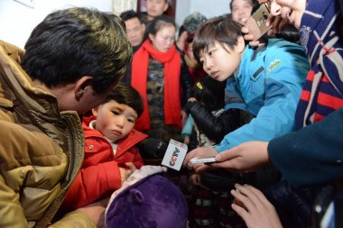 Five-year-old girl Yiran, second left, who was kidnapped and later rescued by police, reunites with her parents at home in Lidong village, Taihe county, Fuyang city, east China's Anhui province, 6 January 2016