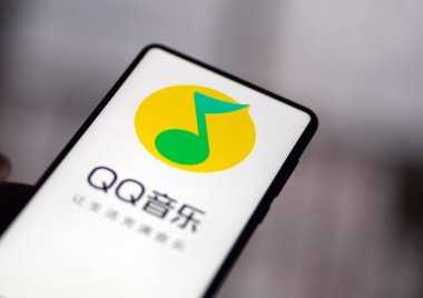 A Chinese resident uses the app of QQ Music of Tencent Music Entertainment Group (TME) on his smartphone in Ji'nan city, east China's Shandong province, 3 January 2019