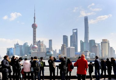 --FILE--Tourists view of take photos of the skyline of the Lujiazui Financial District with skyscrapers and high-rise buildings in Pudong from the promenade on the Bund in Shanghai, China, 31 January 2015