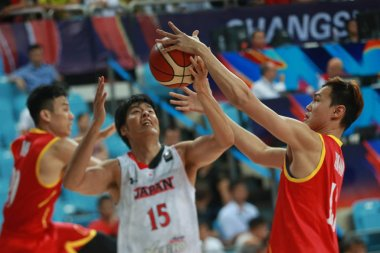 A player of Malaysia, right, challenges Joji Takeuchi of Japan in a group match during the 2015 FIBA Asia Champions for Men in Changsha city, central China's Hubei province, 24 September 2015
