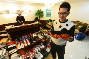 30-year-old Chinese man Mick, the owner of 283 pairs of Nike Jordan sneakers, looks at the shoes he pawned off to make down-payment on an apartment at the pawn shop of Beijing World of Pawn Co., Ltd. in Beijing, China, 9 February 2015