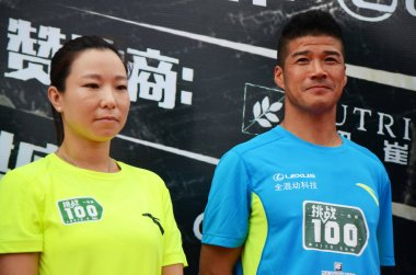 China's first international ultra-marathon champion Chen Penbin, right, and Chinese tennis player Zheng Jie attend the ceremony to start the challenge of running 100 marathons in 100 consecutive days in Guangzhou city, south China's Guangdong provinc