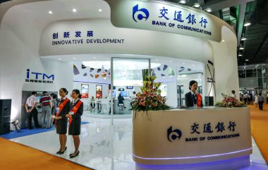 Chinese employees are seen at the stand of Bank of Communications (BoCom) during an exhibition in Guangzhou city, south China's Guangdong province, 23 June 2013