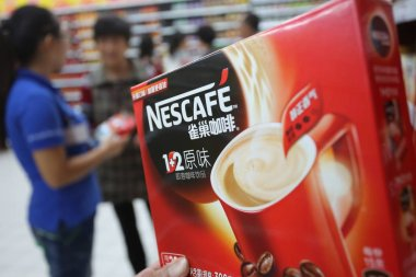 A customer shops for a carton of Nescafe instant coffee of Nestle at a supermarket in Xuchang city, central China's Henan province, 26 October 2014