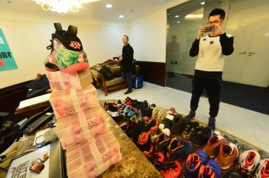30-year-old Chinese man Mick, left, the owner of 283 pairs of Nike Jordan sneakers, takes photos of bricks of 100-yuan RMB (Renminbi) banknotes after pawning off the shoes to make down-payment on an apartment at the pawn shop of Beijing World of Pawn