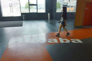 An employee walks over the logo of Chinese e-commerce giant Alibaba at the headquarters of Alibaba in Hangzhou city, east China's Zhejiang province, 18 May 2015