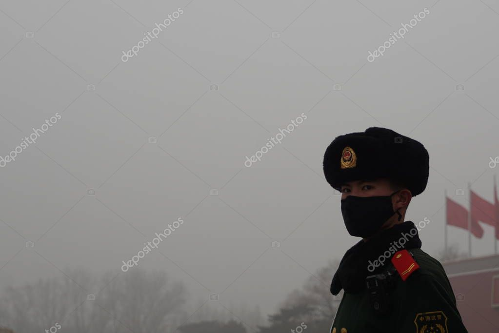 --FILE--A Chinese paramilitary policeman wearing a face mask against air pollution stands guard on the Tiananmen Square in heavy smog in Beijing, China, 26 December 2015.
