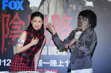 Japanese actress Chie Tanaka, left, is fed by a performer acting a zombie at a press conference for the broadcast of American TV series